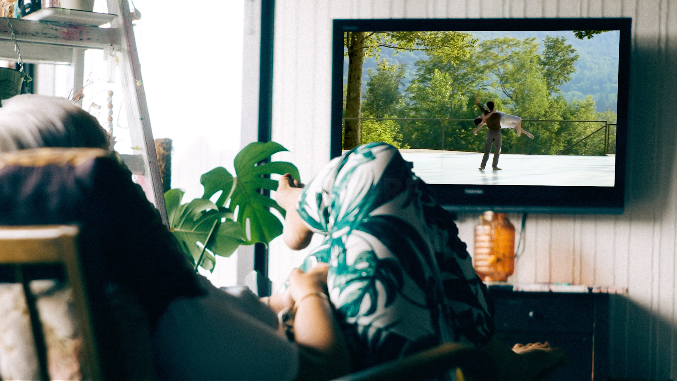 Person sitting on couch watch a Jacob's Pillow dance performance on their TV.