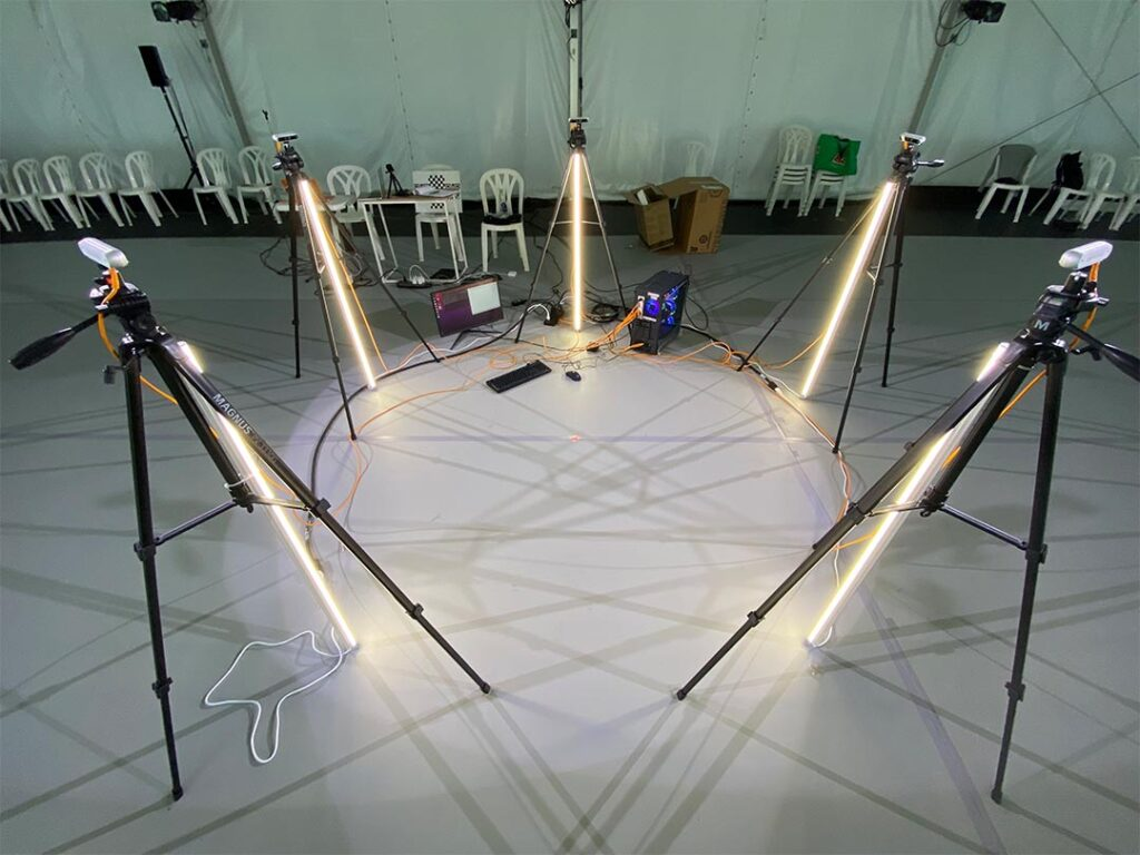 Five cameras on tripods arranged in a circle.