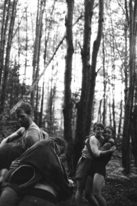 Black and white photo of people dancing in the woods.