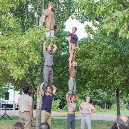 Two groups of people standing three people high on top of each others' shoulders in a park.