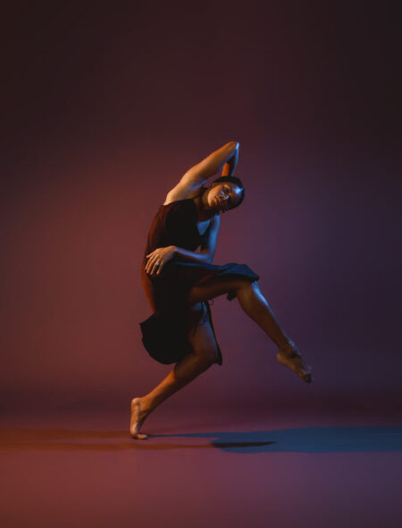Dancer Ausia Jones stands on her left toes, crossing her bent right leg across her body and folding her right arm over her head. Her left arm wraps around her body. The lighting is tinged with dark blue and orange hues.